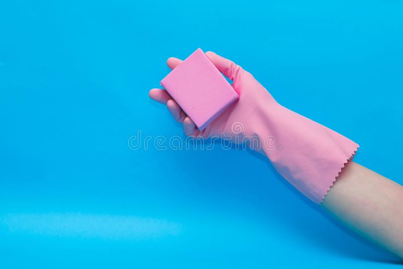 Mano in guanto rosa con la spugna rosa su fondo blu fotografia stock