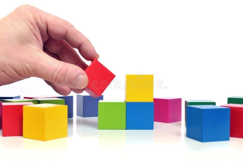 Mano humana con los bloques del juguete fotografía de archivo