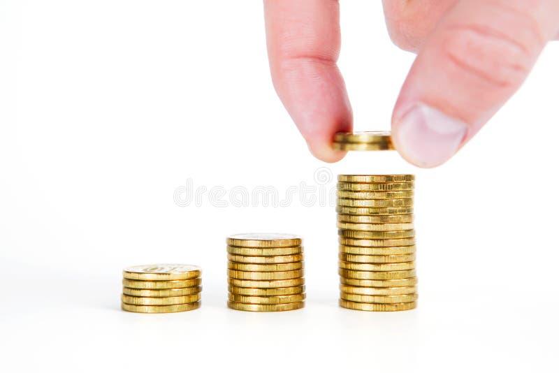 Mano humana de la mano que pone la moneda al dinero imagen de archivo