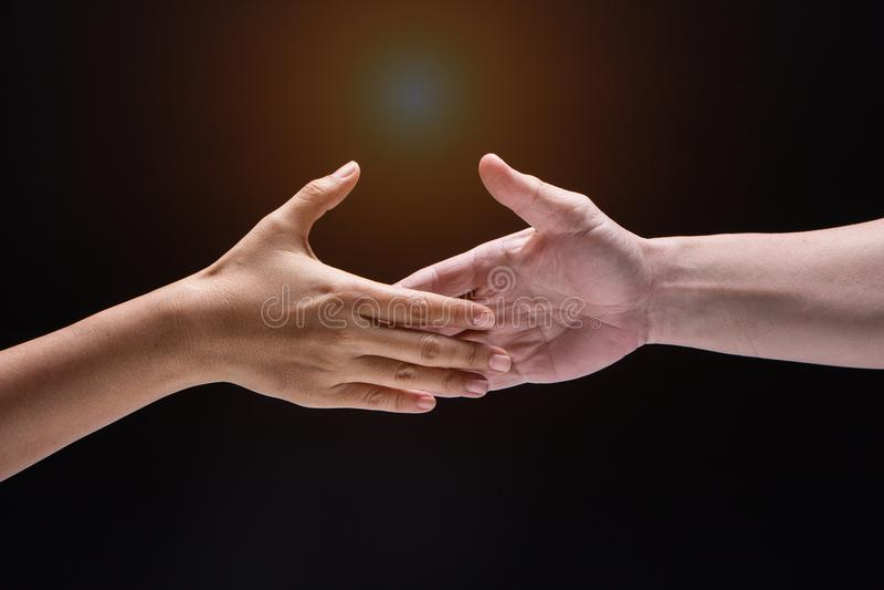 Mano humana del primer, entre el mand y la mujer están alcanzando para tocar juntos, la muestra y el símbolo de la amistad fotografía de archivo libre de regalías