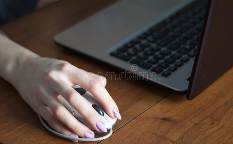 Mano humana en ratón del ordenador Computadora portátil en el escritorio fotografía de archivo