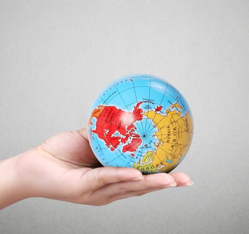 Mano humana que lleva a cabo elementos del globo de la imagen suministrados por la NASA foto de archivo libre de regalías
