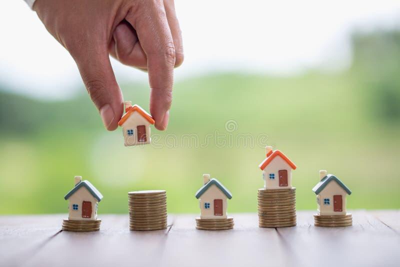 Mano humana que pone el modelo de la casa en pila de las monedas, el dinero de planificaci?n de los ahorros de monedas para compr foto de archivo libre de regalías