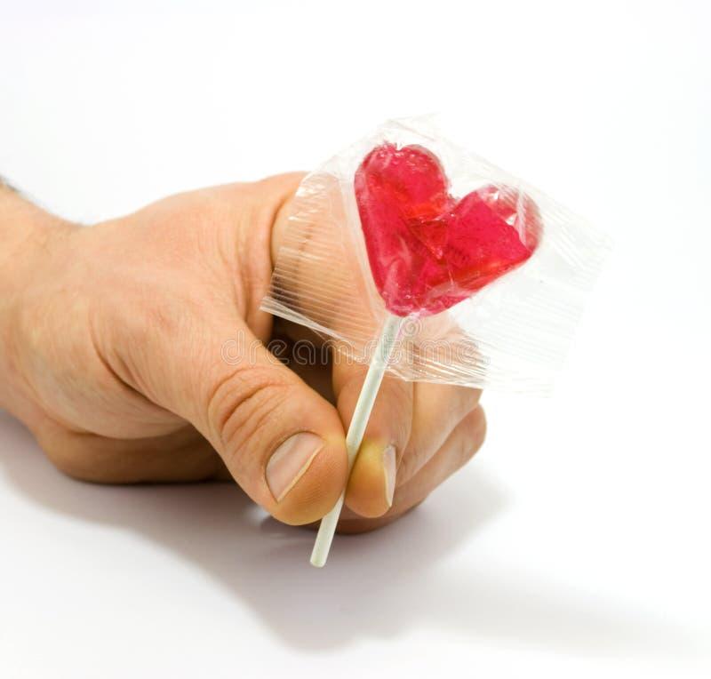 Mano humana que sostiene el caramelo en forma de corazón imagen de archivo