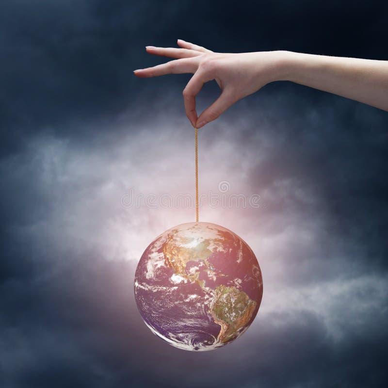 Mano humana que sostiene el planeta de la tierra en cuerda imagen de archivo