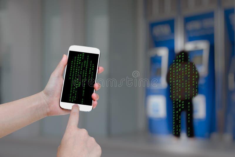 Mano humana que sostiene el teléfono elegante móvil con el fondo de la falta de definición de la máquina de caja automática fotografía de archivo