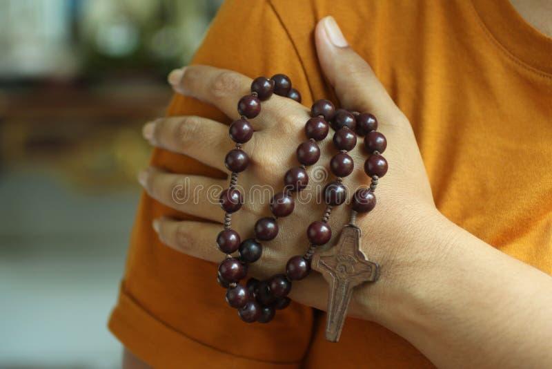 Mano humana que sostiene un rosario en el hombro Manos menores del hombre joven que ruegan sosteniendo un rosario con Jesus Chris fotografía de archivo