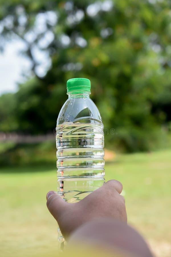 Mano humana que sostiene una botella de agua imagenes de archivo