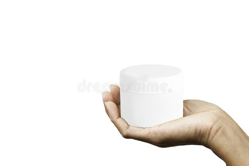 Mano isolata che tiene barattolo cosmetico bianco su un fondo bianco con il percorso di ritaglio immagini stock