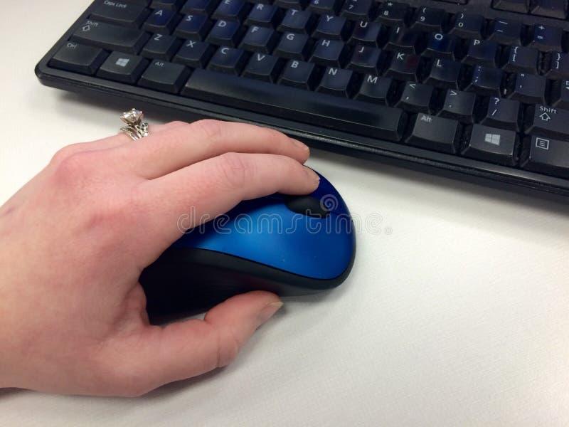 Mano izquierda usando un ratón del ordenador fotografía de archivo