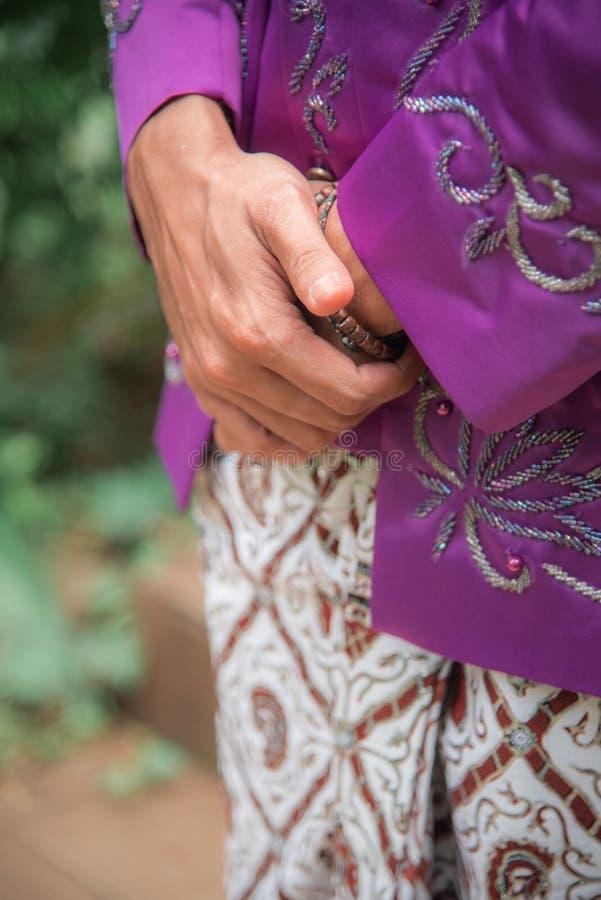 Mano Javanese del plegamiento del novio que lleva los sarong tradicionales del batik Gesto de mano de esperar respetuoso y educad fotos de archivo