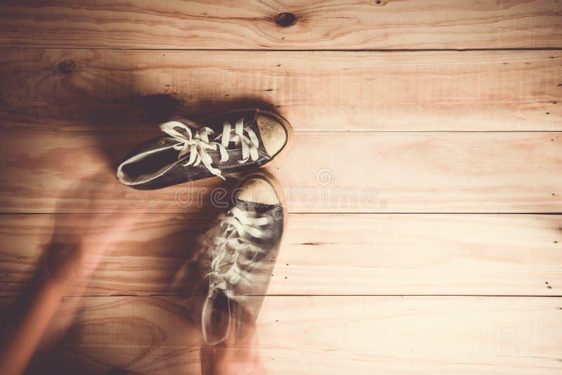 mano móvil con los zapatos en el fondo de madera fotografía de archivo libre de regalías