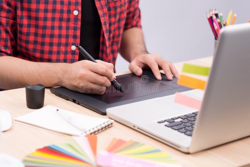 Mano maschio che attinge la tavola del grafico nell'ufficio, primo piano immagine stock