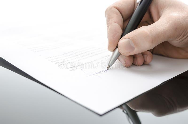 Mano maschio che firma un contratto su una tabella nera fotografia stock