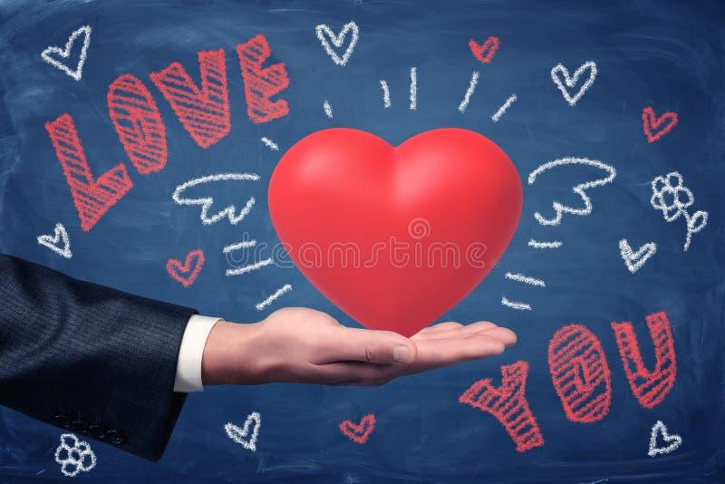 Mano maschio che tiene cuore rosso con AMORE VOI disegni del segno e del cuore del gesso su fondo blu fotografie stock
