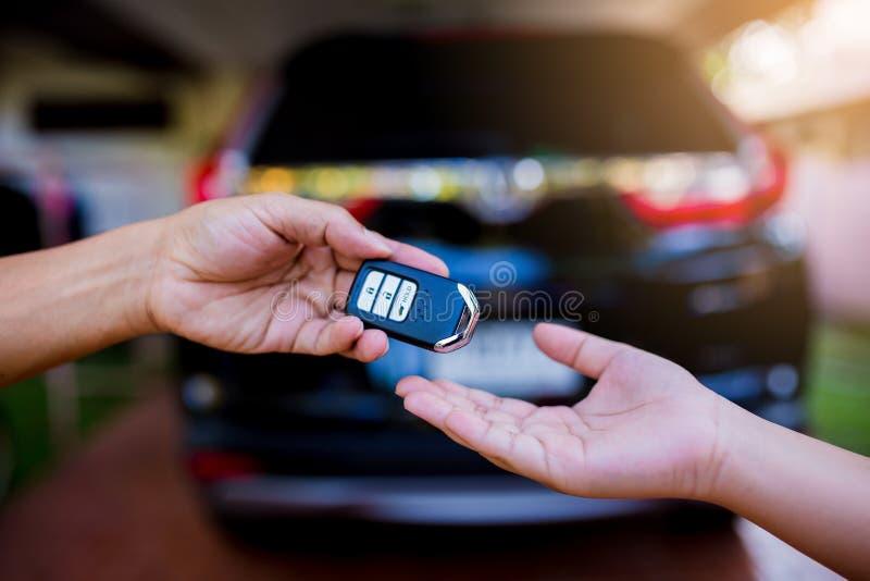 Mano maschio che tiene una chiave a distanza dell'automobile e che la passa più per dare a fotografie stock libere da diritti