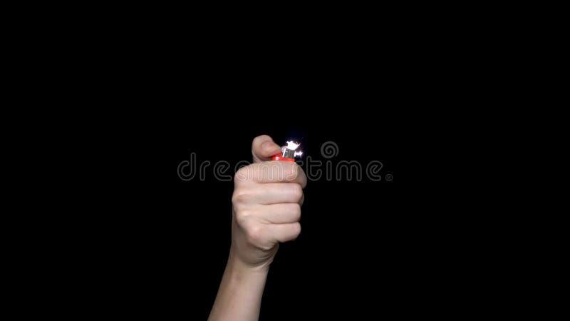 Mano maschio che tiene una luce rossa, isolata su fondo bianco Accendino di gas bruciante della tenuta della mano fotografia stock libera da diritti