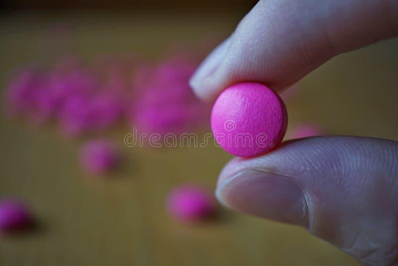 Mano maschio che tiene una pillola rosa come simbolo della farmacia immagine stock
