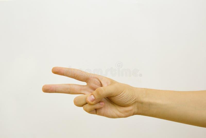 Mano maschio con due dita su nel simbolo di vittoria o di pace Isolato su priorità bassa bianca fotografie stock