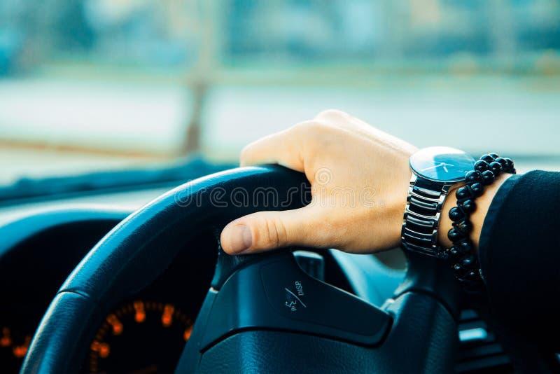 Mano maschio con il braccialetto e l'orologio che conducono un'automobile immagine stock