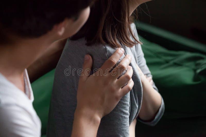 Mano maschio d'aiuto che tiene il primo piano femminile della spalla, psicologico immagine stock libera da diritti