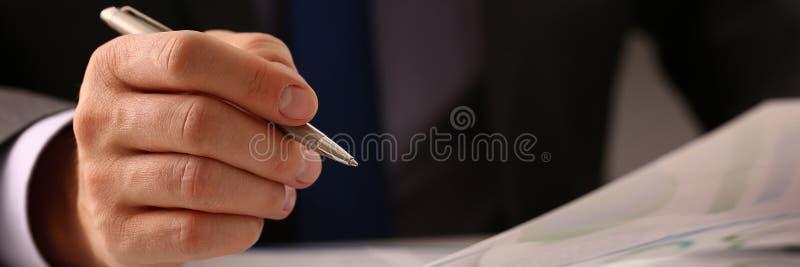 Mano maschio nella penna del siver della tenuta del vestito in ufficio fotografie stock