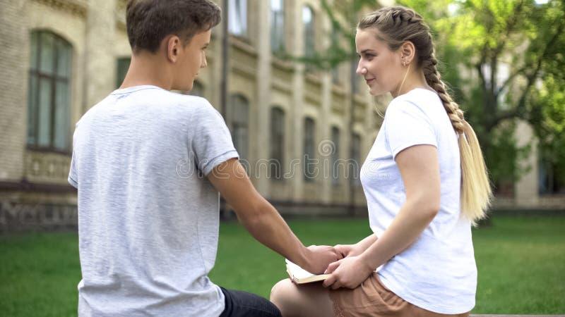 Mano masculina adolescente seria de las muchachas que se sostiene mientras que ella libro de lectura, primera relaci?n imagen de archivo libre de regalías