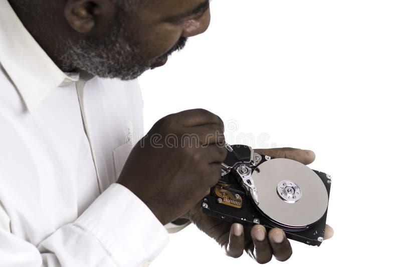 Mano masculina afroamericana del técnico que se sostiene y que trabaja en disco duro del ordenador con destornillador imágenes de archivo libres de regalías