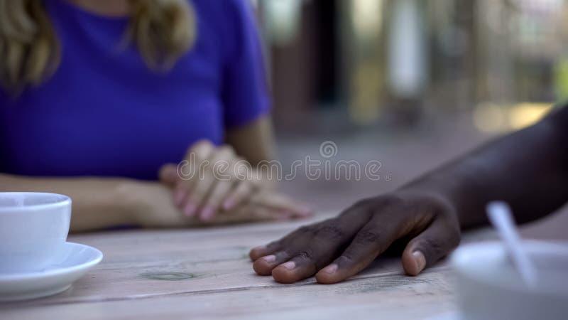 Mano masculina afroamericana en la tabla, mujer caucásica que rechaza tocarla, relación fotos de archivo libres de regalías