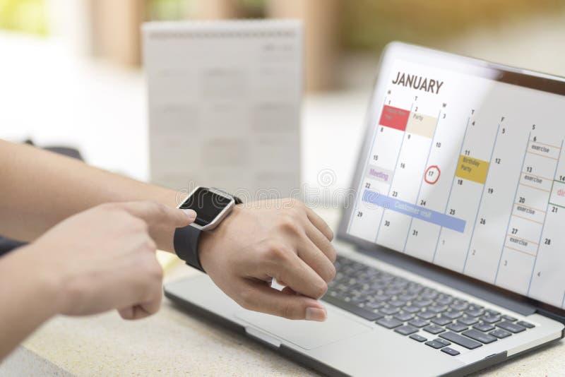 Mano masculina con el reloj elegante en orden del día y horario del planeamiento de la muñeca usando planificador de eventos del  imágenes de archivo libres de regalías