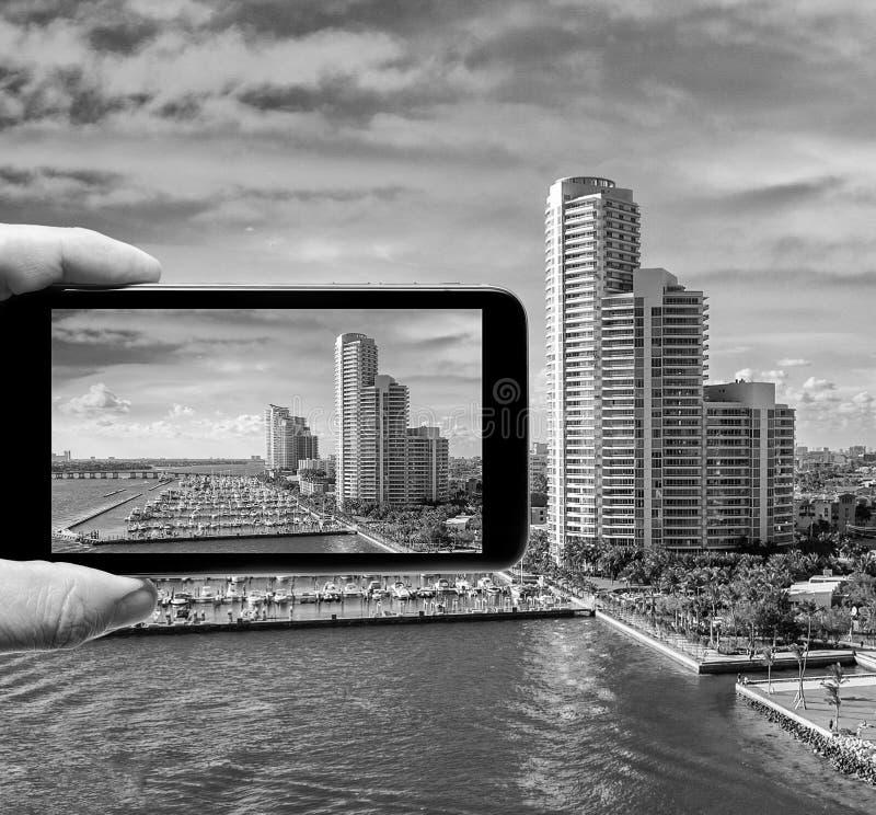 Mano masculina con el smartphone que toma una imagen de Miami de la travesía imagen de archivo