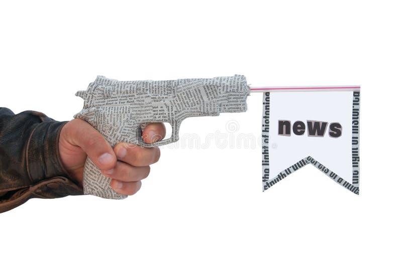 Mano masculina con la pistola y el indicador shoting del periódico foto de archivo