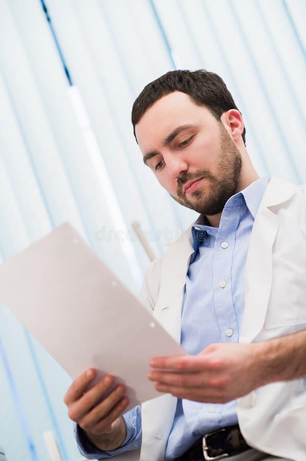 Mano masculina del doctor de la medicina que sostiene los papeles Guarde la ronda, el control paciente de la visita, el cálculo m imagenes de archivo