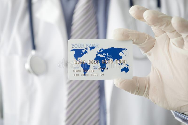 Mano masculina del doctor en el control blanco de los guantes protectores fotografía de archivo