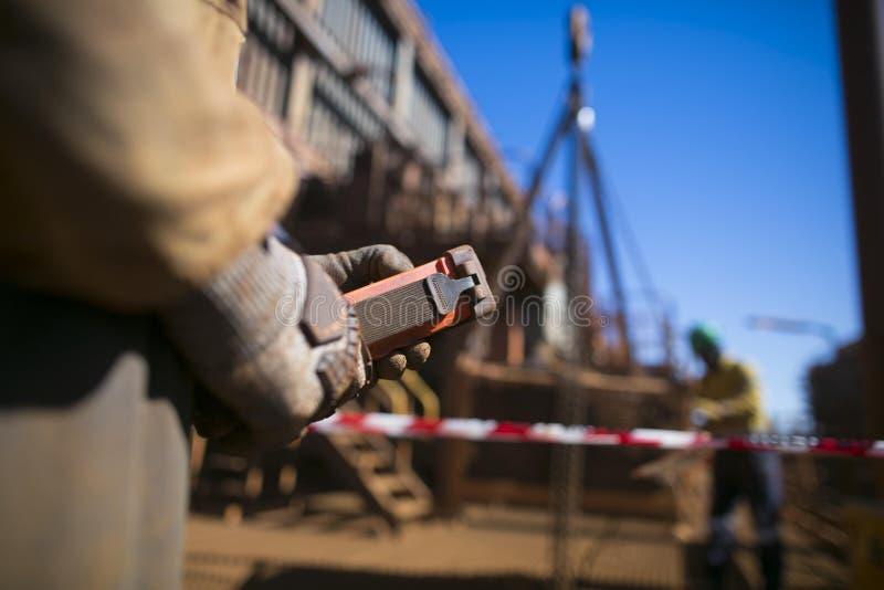 Mano masculina del instalador que controla la carga de elevación remota de la grúa roja del alzamiento mientras que imagen borros fotos de archivo