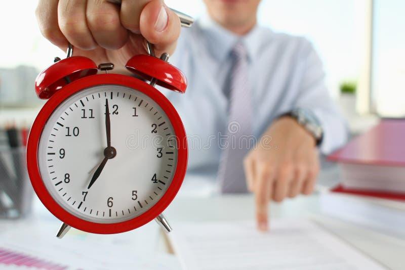 Mano masculina en el despertador un rojo fotografía de archivo libre de regalías