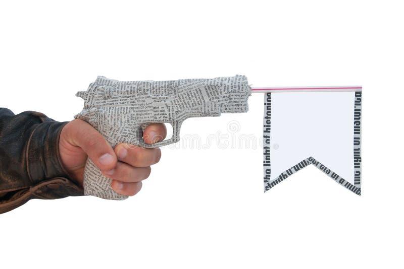 Mano masculina izquierda con el fuego una pistola del periódico del tiro imagen de archivo