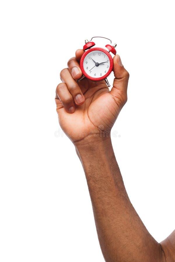 Mano masculina negra que sostiene el despertador rojo fotografía de archivo libre de regalías