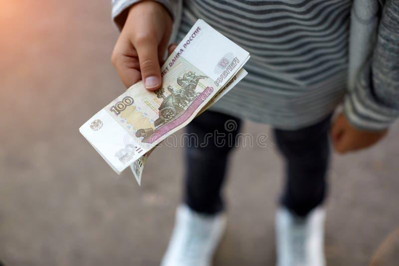 Mano masculina que abre un sobre blanco por completo de la rublo rusa de la moneda rusa, FROTACIÓN en la tabla de madera como sím imágenes de archivo libres de regalías