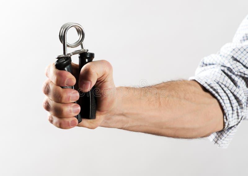 Mano masculina que ejercita fuerza usando el agarrador de la mano imagen de archivo