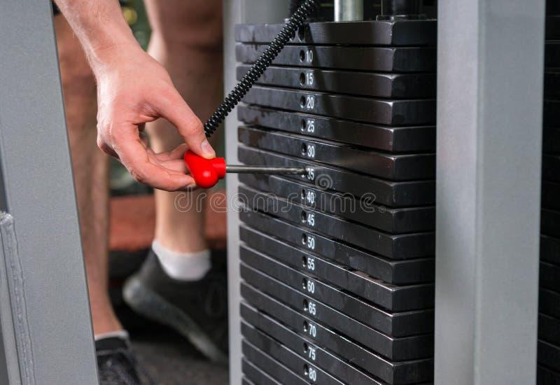 Mano masculina que elige un peso en pesos de un metal del levantamiento de pesas e imagenes de archivo