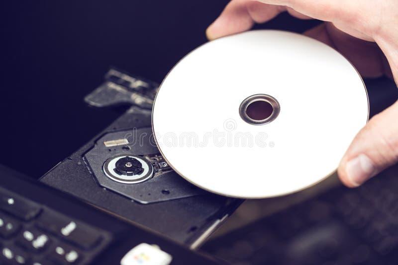 Mano masculina que inserta un DVD en un accionamiento de disco Software o concepto de la instalación de los conductores fotos de archivo