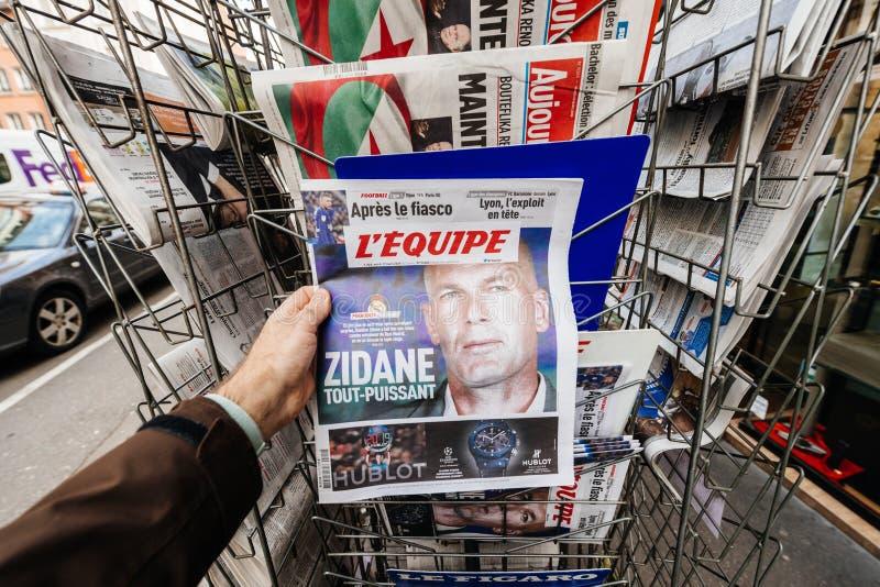 Mano masculina que lleva a cabo l francés 'periódico del deporte de equipo de Equipe foto de archivo