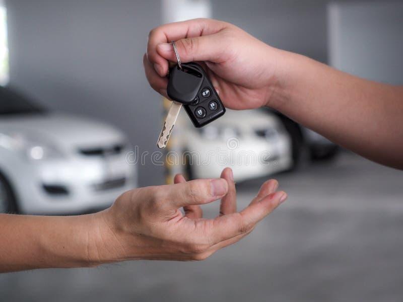 Mano masculina que lleva a cabo un clave del coche y que lo entrega a otra persona foto de archivo libre de regalías