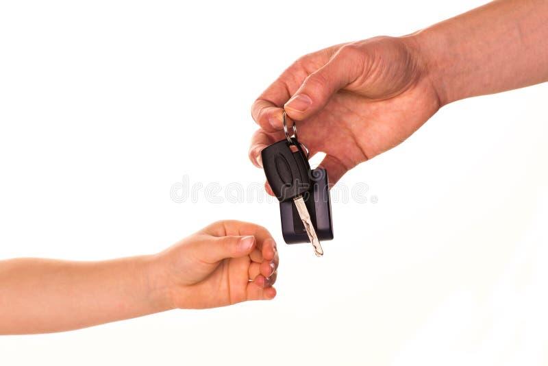 Mano masculina que lleva a cabo un clave del coche y que lo entrega a otra persona imagen de archivo