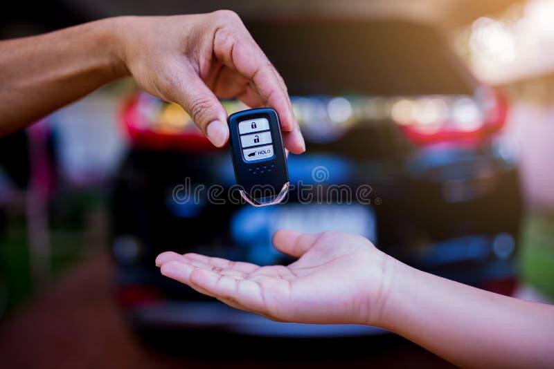 Mano masculina que lleva a cabo una llave remota del coche y que la entrega para dar a fotografía de archivo