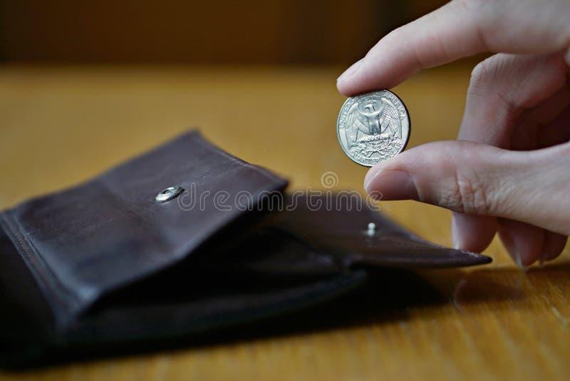 Mano masculina que lleva a cabo una moneda de plata en los E.E.U.U., dólar americano, USD de la moneda del dólar cuarto imágenes de archivo libres de regalías