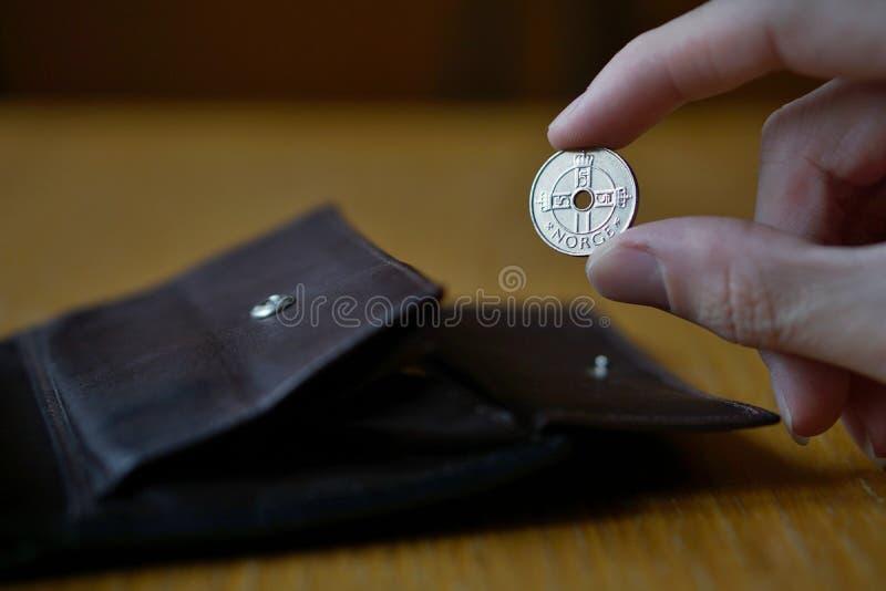 Mano masculina que lleva a cabo una moneda noruega de plata de la moneda en Noruega, corona noruega, NOK imágenes de archivo libres de regalías