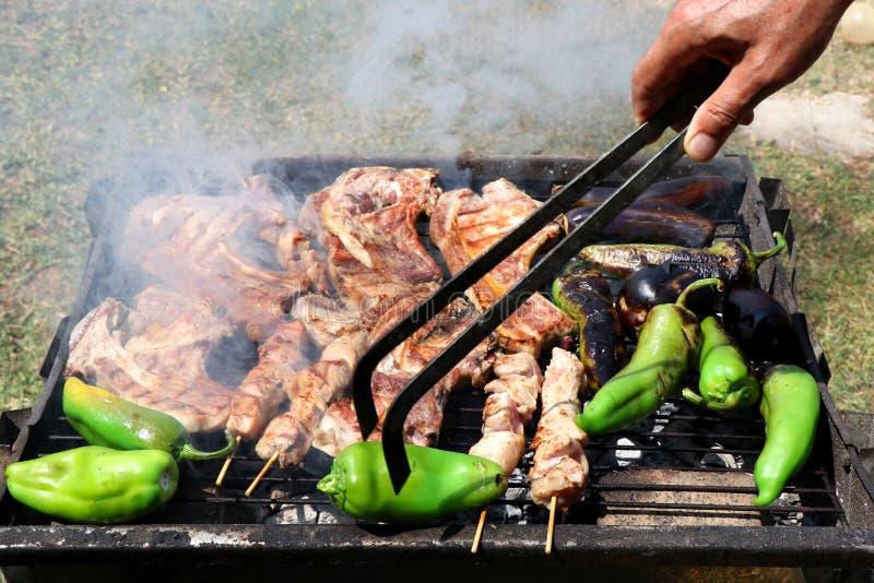 Mano masculina que mueve de un tirón la comida en parrilla de la barbacoa Filetes, kebabs y pimientas fotos de archivo