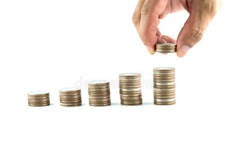 Mano masculina que pone negocio cada vez mayor de la pila de la moneda del dinero en el fondo blanco foto de archivo libre de regalías